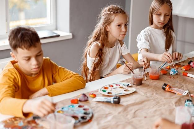 学校でカラフルな絵の具で紙に絵を描く子供たち