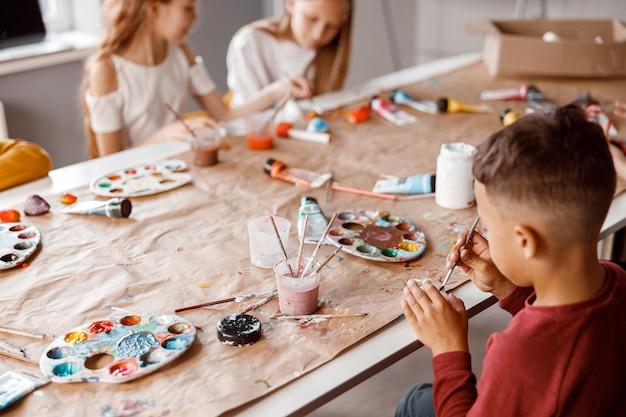 カラフルな絵の具で紙に絵を描く子供たち