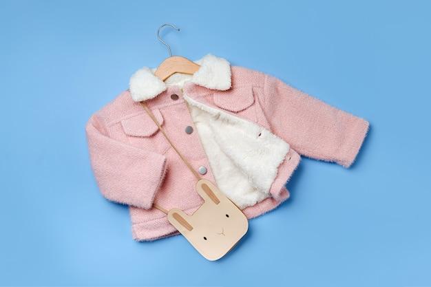 파란색 배경에 귀여운 가방이 달린 옷걸이에 매달려 있는 어린이 분홍색 모피 재킷. 스타일리시한 아동복. 겨울 패션 복장