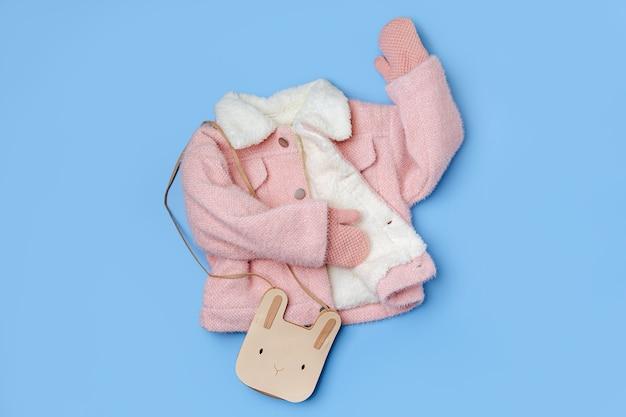 파란색 배경에 귀여운 가방이 달린 어린이 분홍색 모피 재킷. 스타일리시한 아동복. 겨울 패션 복장