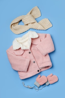 파란색 배경에 스카프가 달린 어린이 분홍색 모피 재킷. 스타일리시한 아동복. 겨울 패션 복장