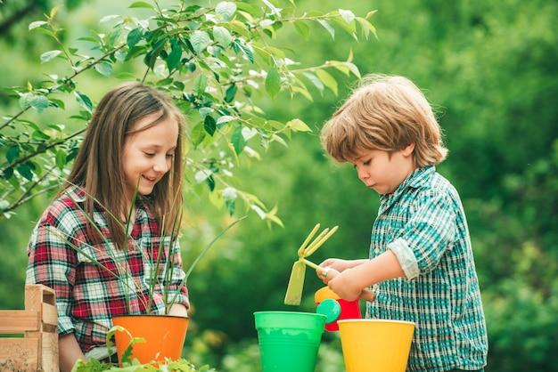 냄비에 꽃을 심는 아이들 2명의 행복한 어린이 농부들이 스프링 필드에서 스퍼드를 가지고 일하고 있다