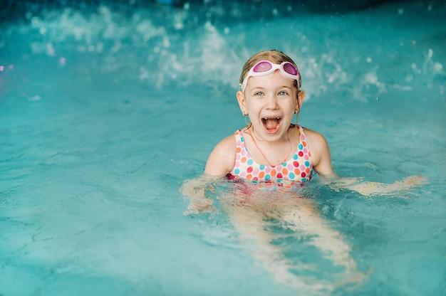 아이들은 아쿠아 파크에서 놀고 있습니다. 열 대 놀이 공원의 물 놀이터에서 어린이. 수영장에서 어린 소녀입니다. 물에서 노는 아이. 어린 아이를 위한 수영복.