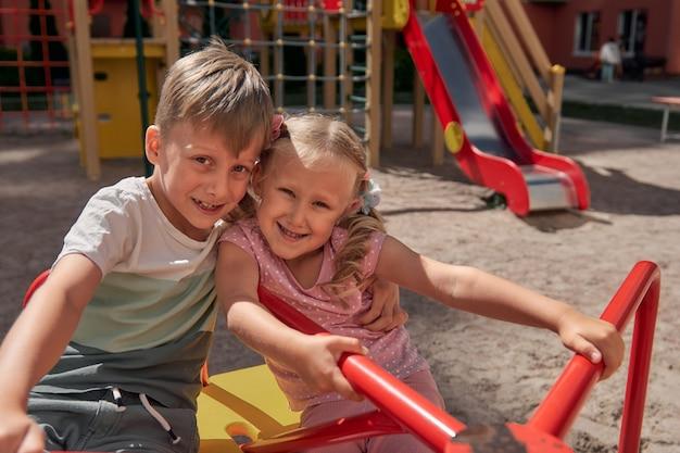 아이들은 놀이터에서 놀고 있습니다. 행복한 웃고 있는 소년과 소녀는 그네와 등반을 즐깁니다. 야외 활동
