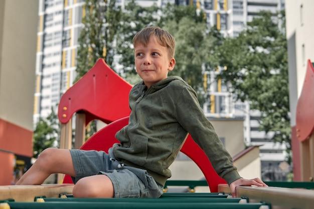아이들은 놀이터에서 놀고 있습니다. 행복한 웃고 있는 소년과 소녀는 야외에서 그네와 등반을 즐긴다