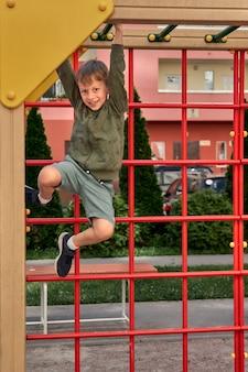 아이들은 놀이터에서 놀고 있습니다. 행복한 웃고 있는 소년은 스윙과 등반을 즐깁니다. 야외 활동