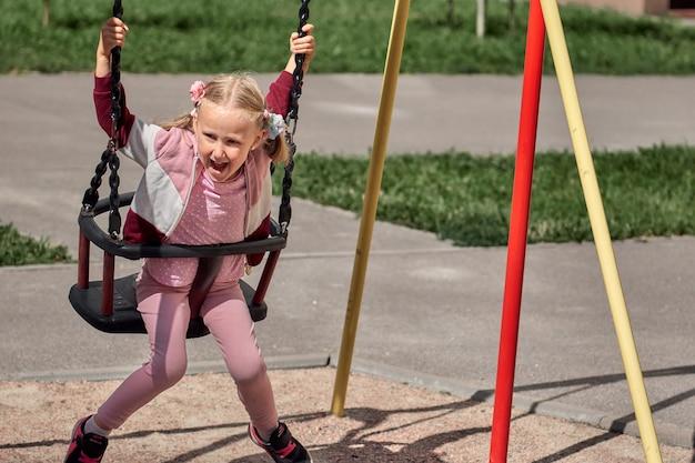아이들은 놀이터에서 놀고 있습니다. 행복한 웃고 있는 소녀는 스윙과 등반을 즐깁니다. 야외 활동