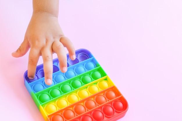 팝 잇 감각 장난감을 가지고 노는 아이들. 스트레스와 불안 완화. 스트레스를 받는 어린이와 성인을 위한 트렌디한 실리콘 만지작거리기 게임. 뽀송뽀송한 거품 장난감.