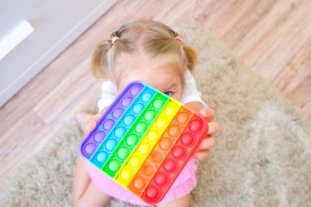 아이들은 팝 잇 감각 장난감을 가지고 놀고 있습니다. 스트레스와 불안 완화. 스트레스 받는 아이들을 위한 트렌디한 실리콘 손놀림 게임