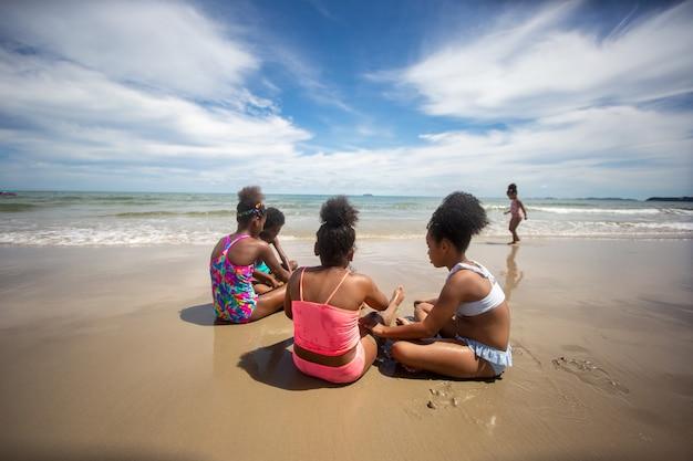 해변에서 모래 위를 달리는 아이들, 여름에 해변에서 손을 잡고 있는 한 무리의 아이들, 바다와 푸른 하늘을 배경으로 한 뒷모습