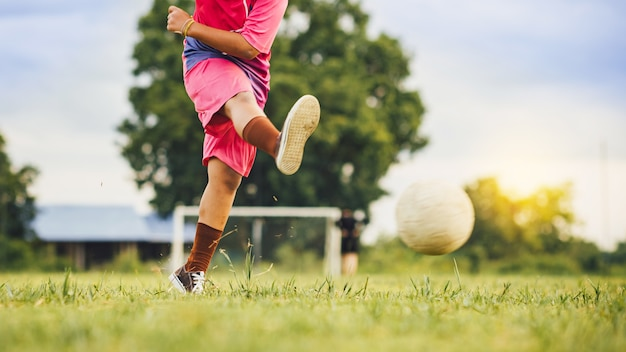 Kids playing soccer football for exercise on the green grass field