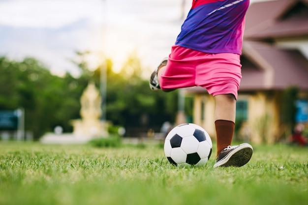 녹색 잔디 필드에서 운동을 위해 축구 축구를 하는 아이들