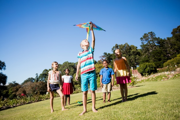 Kids playing together during a sunny day with a kite