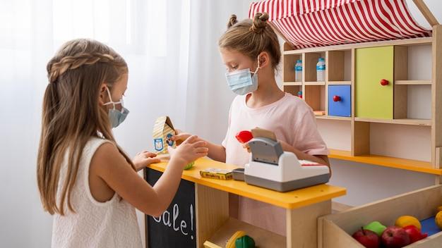 医療用マスクを着用して屋内で一緒に遊ぶ子供たち