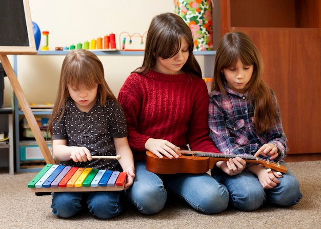 Kids playing together with guitar and xylophone