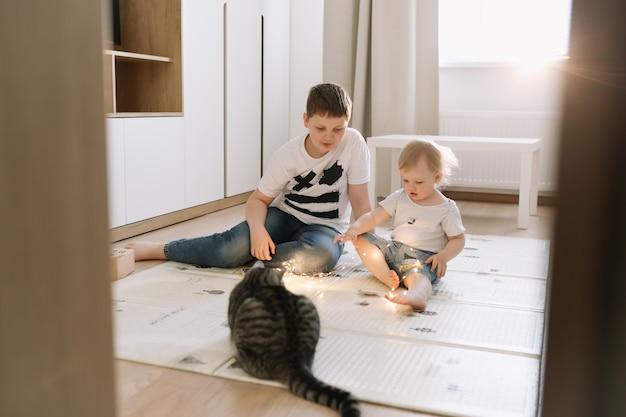 Дети играют с кошкой дома, брат и младшая сестра веселятся вместе