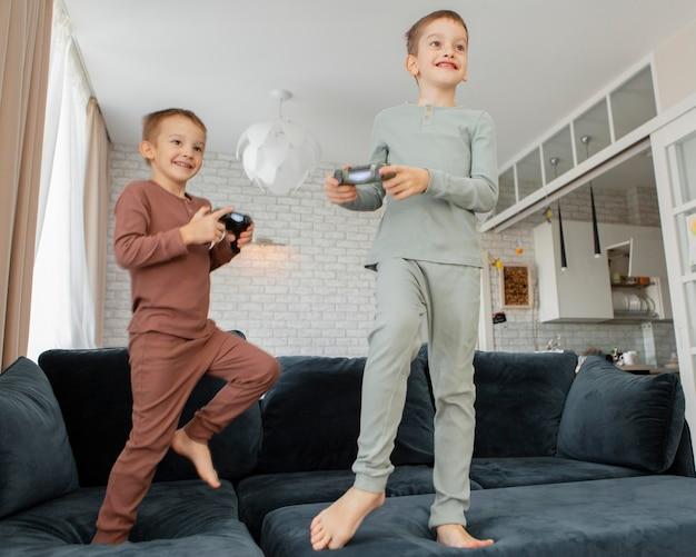 家でコントローラーで遊ぶ子供たち