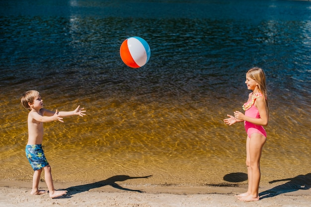 Kids playing with beach ball standing near sea