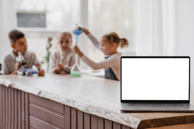 空白の画面のラップトップの横にある化学要素で遊ぶ子供たち