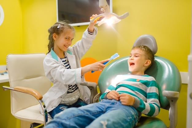 Kids plays medicine worker in imaginary hospital