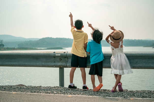 子供たちはダムの美しい景色で空を指す Premium写真