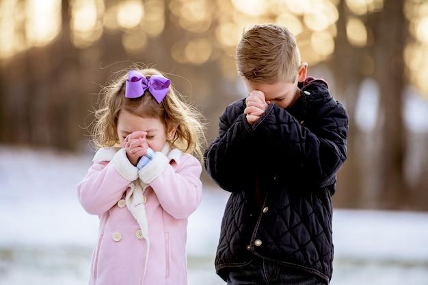 背景がぼやけて雪に覆われた庭で祈る子供たち