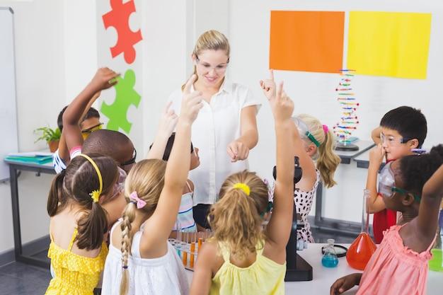 Дети поднимают руку в лаборатории