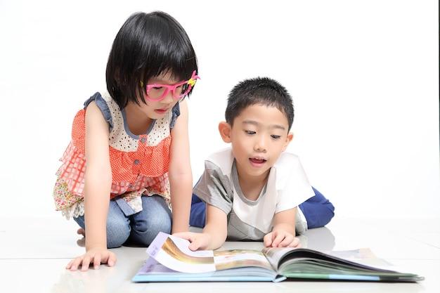 아이들은 흰색 배경과 함께 책을 읽습니다.