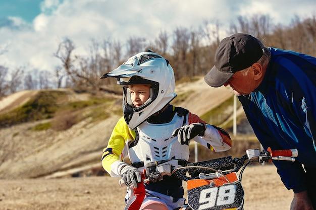 Дети катаются на соревнованиях среди юниоров по мотобайку на мотоцикле тренер дает инструкции своему юному гонщику