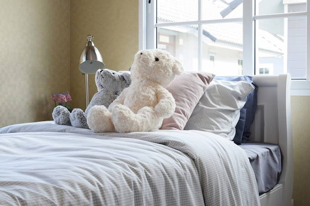 Kids room with dolls and pillows on bed and bedside table lamp
