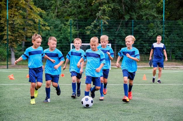 실행 및 어린이 축구 훈련 세션에 축구 공을 차는 아이