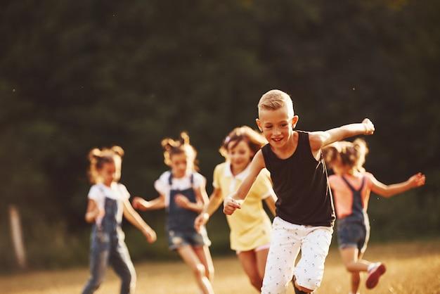 화창한 날 들판에서 뛰어노는 아이들. 건강한 생활 방식의 개념입니다.