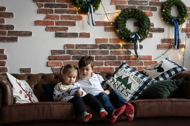 큰 크리스마스 트리 옆에서 책을 읽는 아이 형제