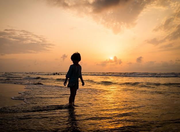 夕日の近くの海のビーチで幸せな時間を持つ子供のシルエット