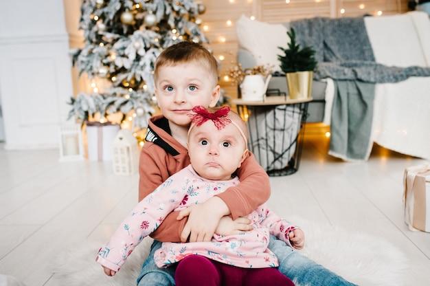 子供たちはクリスマスツリーの近くの床に座って新年あけましておめでとうとメリークリスマス