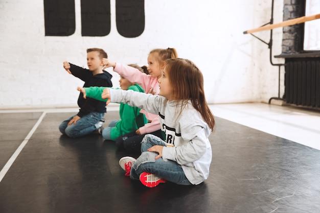 댄스 스쿨에 앉아있는 아이들. 발레, 힙합, 거리, 펑키하고 현대적인 댄서 개념.