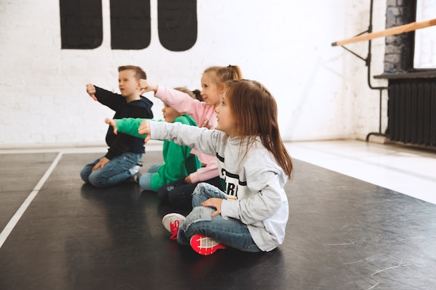 Kids sitting at dance school. ballet, hiphop, street, funky and modern dancers concept.