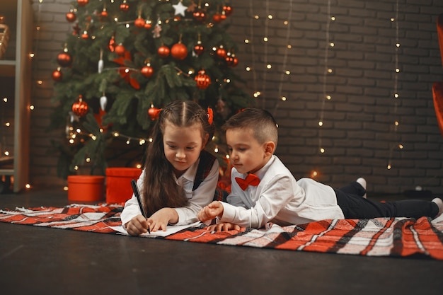 Kids sitting near christmas tree. children write a letter to santa claus.