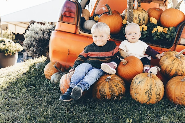 Kids sitting in pile of pumpkins outdoor little girl and boy playing with pumpkins at pumpkin patch