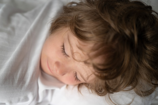 Kids sleeping alone in comfortable bed with white linens.