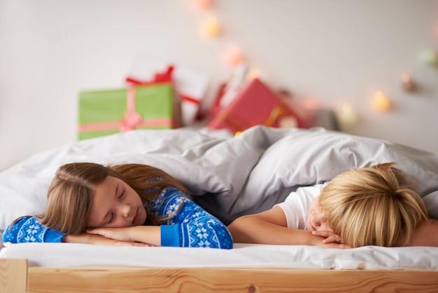 크리스마스에 편안한 침대에서 자고있는 아이들
