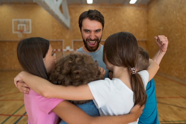 Kids and smiley physical education teacher