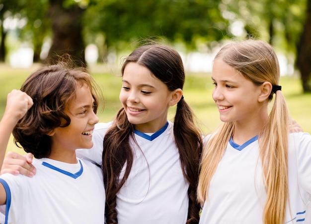 Дети улыбаются после победы в футбольном матче