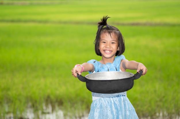 웃 고 흐리게 쌀 필드와 하늘에 음식 냄비를 들고 아이