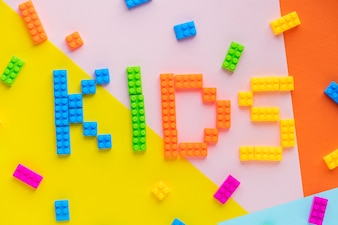 Kids spelled word with plastic blocks background