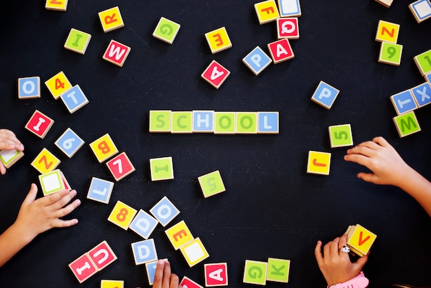 Kids spelling out words with alphabet blocks