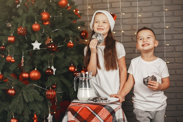 Дети, стоящие возле елки. дети едят печенье с молоком.