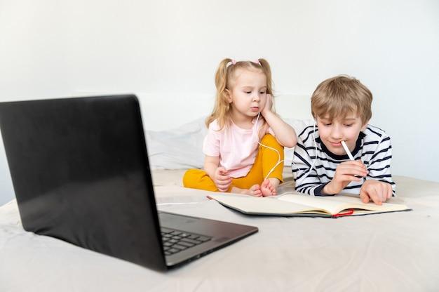 노트북과 헤드폰을 사용하여 집에서 공부하는 아이들