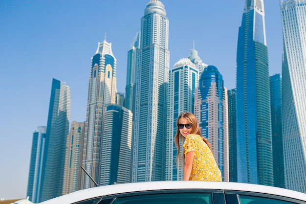 Kids summer vacation. teenager girl on car vacation over skyscrapers in dubai