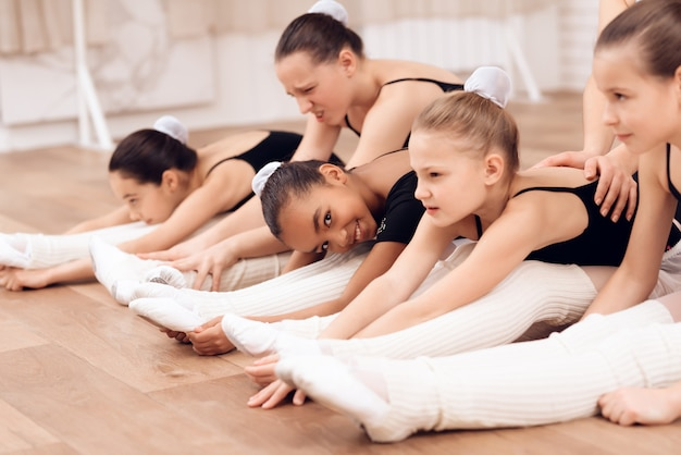 Kids and teacher do ballet workout on a floor.